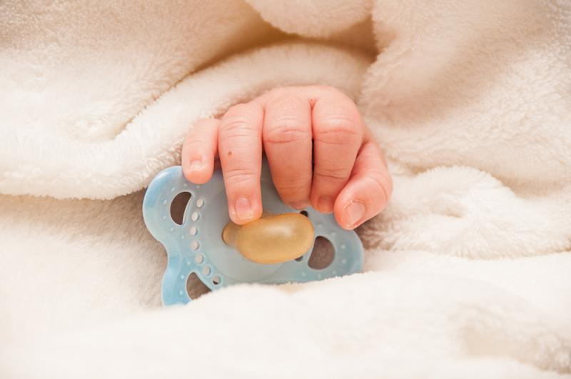 baby_with_pacifier_in_hand